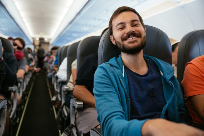 Young smiling man with headphones sitting on an airplane during